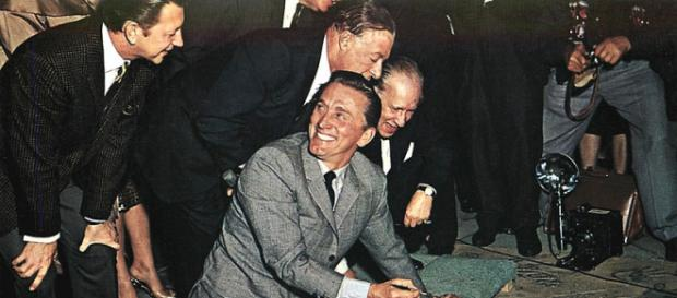 Kirk Douglas signs his name in the wet concrete at Grauman's Chinese Theatre (Image credit – Mitoc and Sons, Wikimedia Commons)