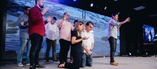 Jair Bolsonaro (de joelhos ao centro, juntamente com a esposa) tem recebido apoio de vários líderes evangélicos (Foto: reprodução)