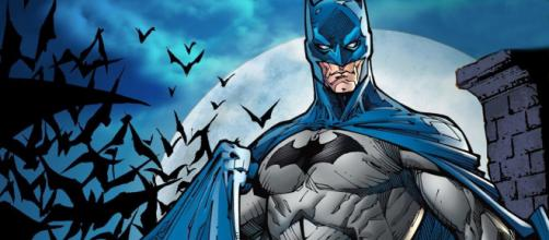 Bruce Wayne como Batman em seu traje azul e cinza.
