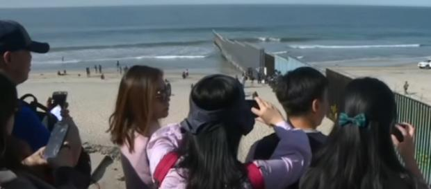 US reinforces border wall in Tijuana as migrants look on. [Image source/AFP News Agency YouTube video]