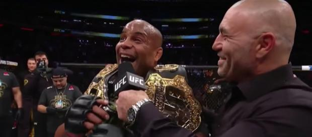 Daniel Cormier grins in excitement with his titles after retaining the UFC Heavyweight Title at UFC 230. - [UFC / YouTube screencap]