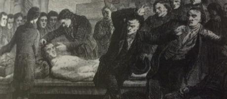 Científicos aplicando corrientes eléctricas a un cadáver durante la era galvánica