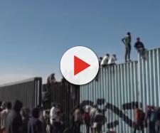 Migrants scale border fence near Tijuana, Mexico. - [AP Archive / YouTube screencap]