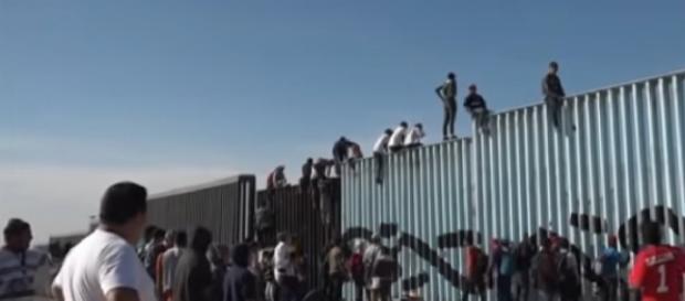 Migrants scale border fence near Tijuana, Mexico. - [AP Archive / YouTube screencap]