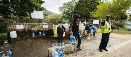Un oficial de seguridad dirige a los residentes mientras llenan botellas de agua en el manantial natural de Newlands en Ciudad del Cabo