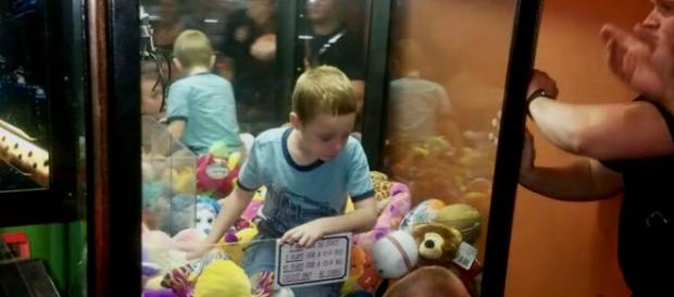 A young boy was so determined to get the toy he wanted, he climbed inside the machine [Image credit: CBS News/YouTube]