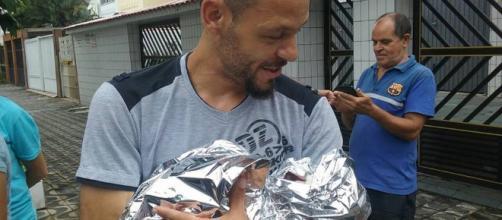 Pai segura filha após ele mesmo realizar o parto. (Foto Reprodução).