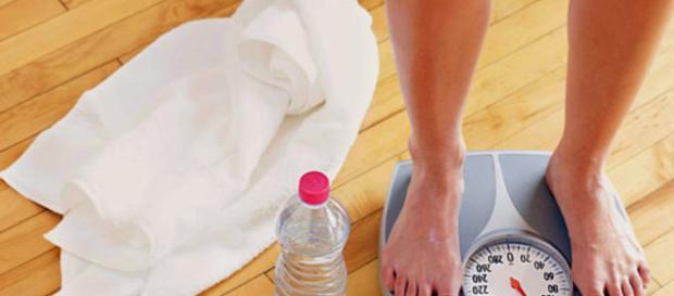 Uma pessoa conferindo seu peso.