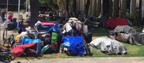 Varias personas sin hogar en sus campamentos el domingo junto al río Santa Ana en Anaheim.