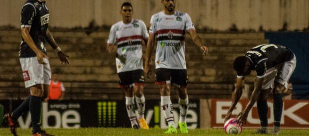Jogadores do São Bento se preparam para lance de falta contra o Botafogo-SP