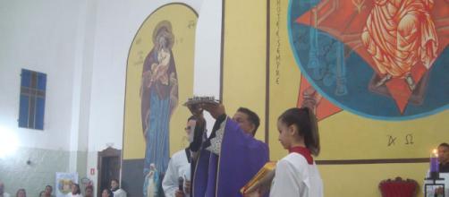 Padre Marcos eleva cinzas diante dos fiéis antes de abençoá-las.