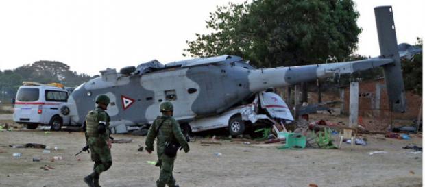 Soldados mexicanos caminan cerca de los restos de un helicóptero militar que se estrelló el viernes en el sur de México.