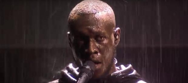 Stormzy had a surge of questions and critique for Theresa May in his Brit awards performance, Image cap Stormzy/YouTube