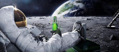 In alto, astronauta intento a bere una birra