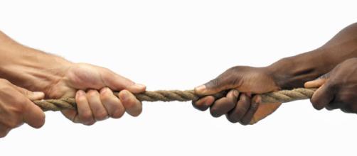 Un uomo bianco e uno nero intenti a tirare una corda