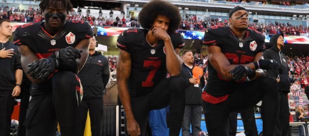 Kaepernick, en el medio, reticente a levantarse durante el himno