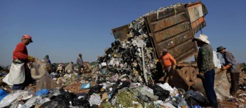 Trabalhadores se reúnem no torno de um caminhão que despeja lixo no aterro Estrutural, em Brasília