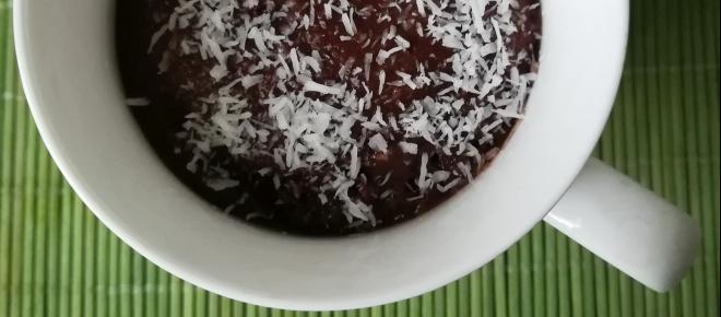 Una golosa mug cake vegana al cioccolato con scaglie di cocco