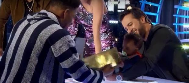 Singing young dad Marcio Donaldson gets his golden 'American Idol' ticket from the judges and his baby son. Screenshot American Idol/YouTube