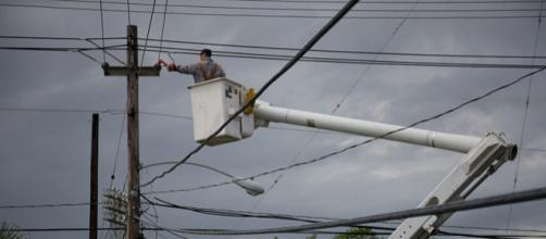 Electric company repairing a power pole in Puerto Rico (Image credit – Andrea Booher, Wikimedia Commons)