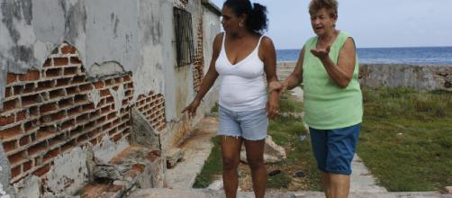 Par de mujeres verificando daños en su vivienda