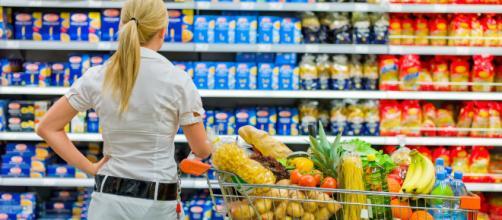 Una consumatrice difronte gli scaffali del supermercato. Le confezioni possono diventare ingannevoli: il prezzo è uguale ma la quantità è minore
