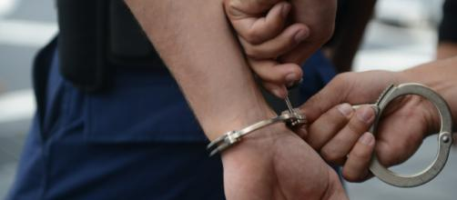 A pair of hands are placed in metal handcuffs. [Image source: Petty Officer 3rd Class Grant DeVuyst - US Coast Guard]