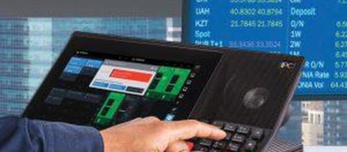 Un lugar de trabajo o estación de un comerciante moderno que consta de cuatro pantallas con datos financieros.