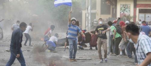 Un manifestante pone en alto la bandera nicaragüense durante los disturbios.