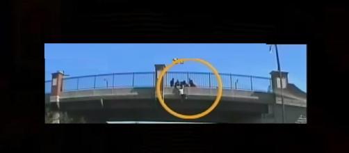 Trucks line up under highway bridge to save jumper. Photo: CBS News/YouTube screenshot