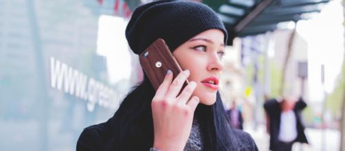 Ragazza cammina con il telefono appoggiato alla testa nonostante le avvertenze dei produttori di telefonini