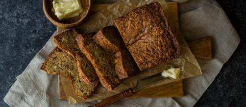 Sliced loaf of banana bread sitting on a cutting board with butter, milk, and a knife di W. Wright