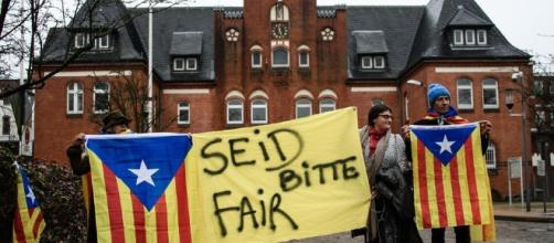 """Varias personas sostienen esteladas y una pancarta en la que se puede leer """"por favor sean justos"""" a las puertas de la prisión de Neumünster. EFE"""