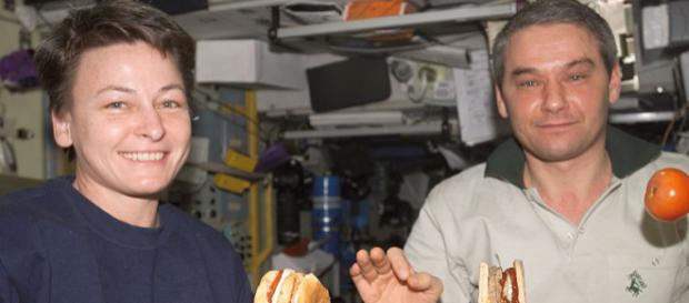 ISS astronauts eating a meal in the Service Module with tomato and hamburger floating (Image credit – NASA, Wikimedia Commons)