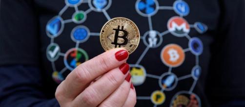 na mujer vestida con una camiseta con logotipos de criptomonedas muestra una representación visual de la criptomoneda Bitcoin.