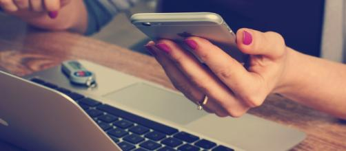 Woman with an iPhone using a Macbook - (Image via FirmBee/Pixabay)