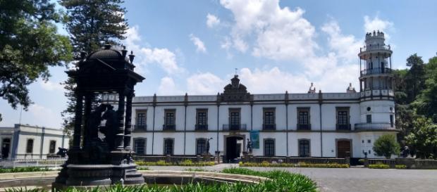 Frente a la fachada del edificio antiguo, la fuente cuya estatua rumorea los secretos del Glez.