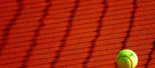 Una pallina da tennis sul campo di terra rossa