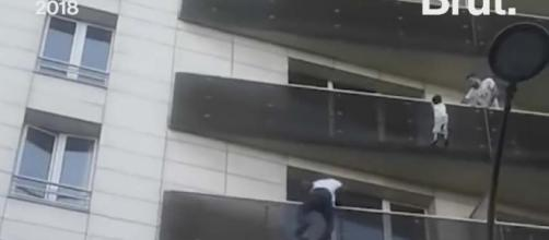 An undocumented migrant from Mali was a hero in Paris when he climbed a building to rescue a small child. [Image: Brut/YouTube]