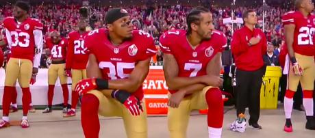 Former teammates Colin Kaepernick and Eric Reid kneel before a game versus the L.A. Rams. [ABC News/YouTube screenshot]