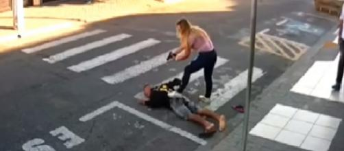 Após ser baleado, assaltante cai no chão e é rendido pela policial (Foto:Reprodução/Youtube)
