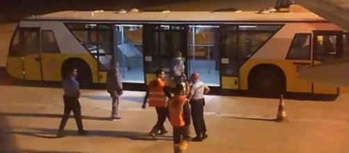 Il passeggero accompagnato dai medici su un pullman dopo l'atterraggio
