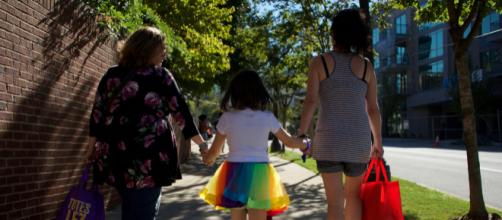A modern family walking away from a gay festival in Atlanta. (Image via Tom Driggers / Flickr)