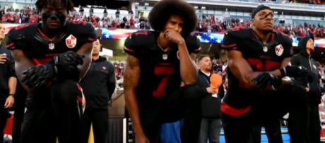 Colin Kaepernick kneels in protest. - [CBS News / YouTube screencap]