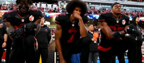 Colin Kaepernick kneels in protest. - [CBS News / YouTube screencap]