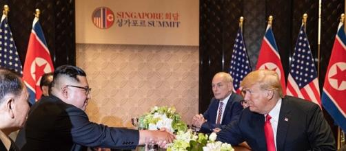 Kim and Trump shake hands across a table at the Singapore Summit (Image courtesy - Dan Scavino Jr., Wikimedia Commons)