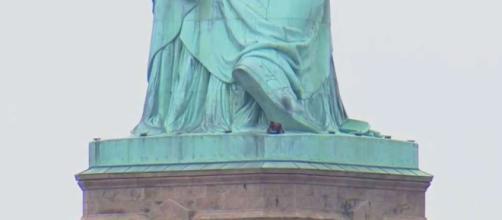 NUEVA YORK / Una mujer se sube a a la base de la Estatua de la Libertad como protesta