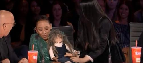 Mel B gets a doll and a diabolical scare she doesn't want from The Sacred Riana on 'America's Got Talent.' [Image Source: AGT - YouTube]