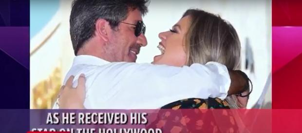 Kelly Clarkson gave warm words to Simon Cowell and got a warm hug at his Walk of Fame ceremony. - [Access / YouTube screencap]