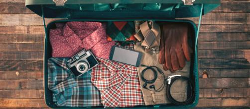 Mala de viagem organizada, com alguns itens, como roupas, máquina fotográfica e celular. (foto reprodução)